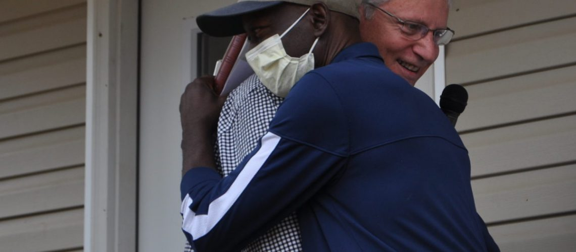 Board member Kevin Underwood congratulates new homeowner Ivory Joe Hayes (in mask) during the dedication of his new home.